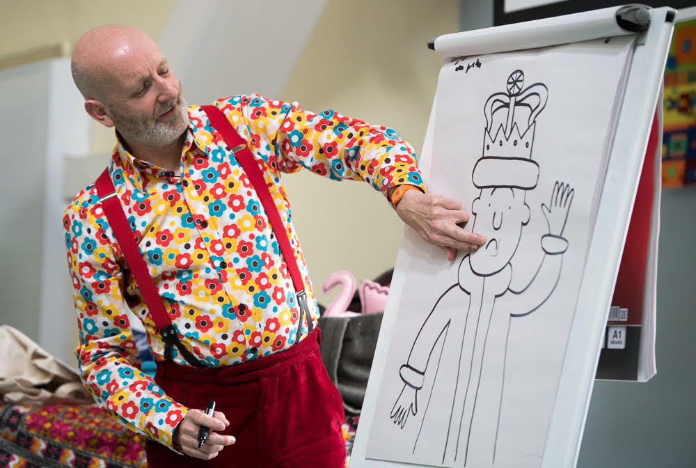 A man in a brightly-coloured shirt draws a cartoon of a king.